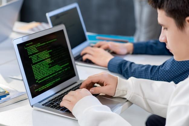 Uno de los estudiantes o programadores frente a la computadora portátil ingresando datos técnicos mientras mira la pantalla durante el trabajo sobre un nuevo software