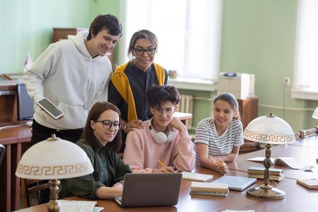 Estudiantes ocasionales viendo una lección de video en línea en una computadora portátil mientras se preparan para una conferencia o seminario en la biblioteca de la universidad