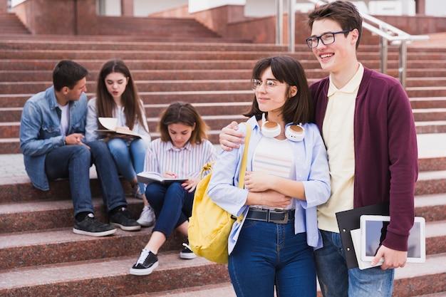 Estudiantes parados abrazando y sosteniendo libros
