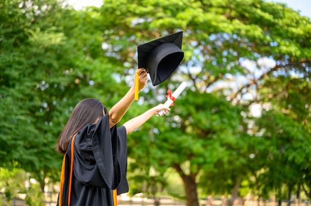 Estudiantes de pelo largo vestidos con volantes negros que expresan alegría en la graduación de la universidad.