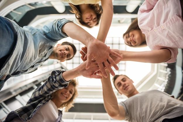 Estudiantes de pie en círculo y juntando las manos.