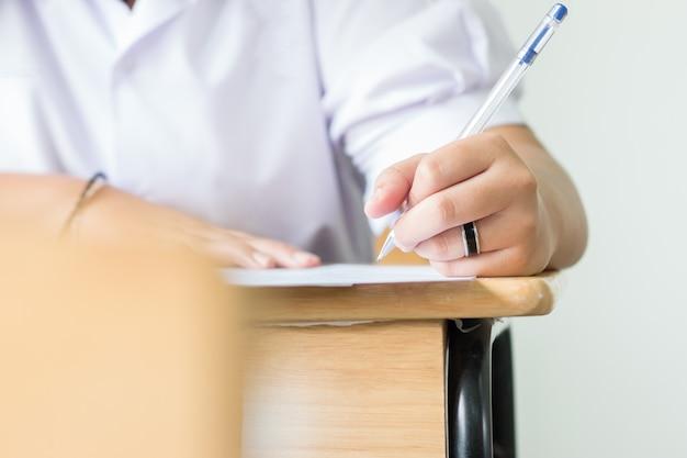 Estudiantes con pluma en las manos tomando exámenes