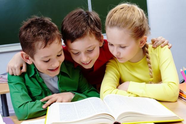 Estudiantes de primaria leyendo un libro amarillo con la pizarra de fondo
