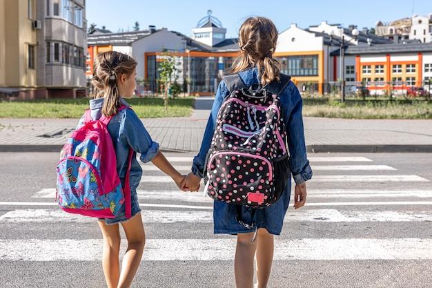 Los estudiantes de primaria van a la escuela tomados de la mano el primer día de clases de regreso a la escuela