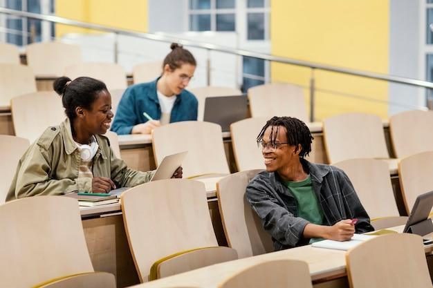 Estudiantes que asisten a una clase universitaria.