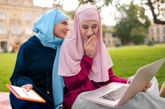 Estudiantes que buscan información. estudiantes musulmanes internacionales que buscan información en internet mientras están sentados afuera