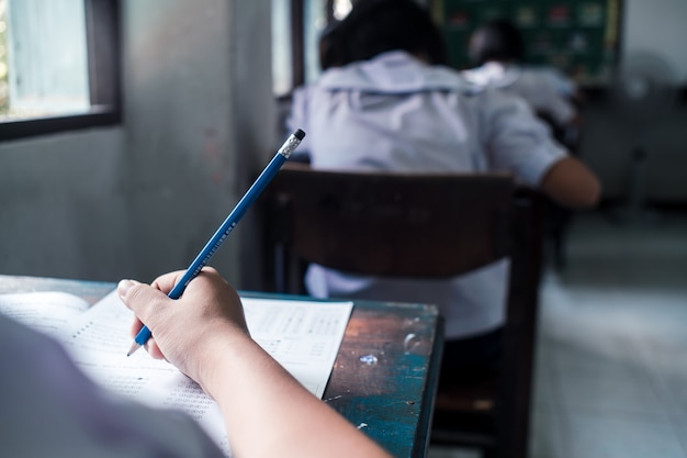 Estudiantes que escriben y leen las hojas de respuestas del examen ejercicios en la escuela con estrés
