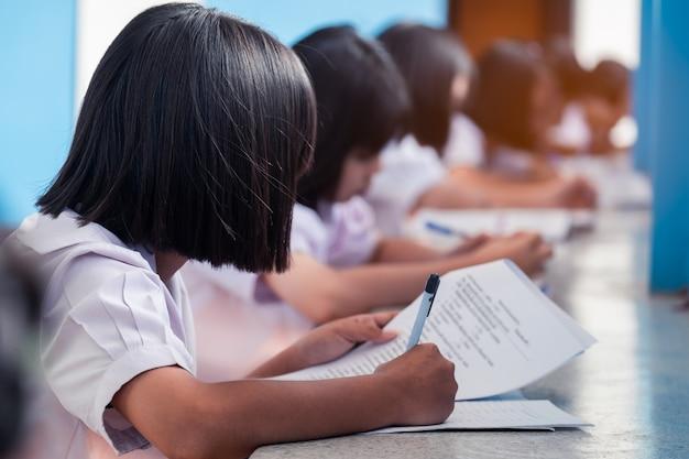 Estudiantes que escriben y leen hojas de respuestas de exámenes en la escuela con estrés
