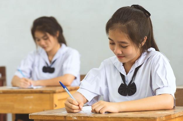 Los estudiantes que escriben con la pluma en la mano haciendo exámenes, hojas de respuestas, ejercicios en el aula con estrés.