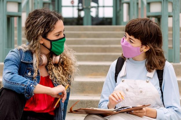 Estudiantes que estudian al aire libre en la escuela en la nueva normalidad.