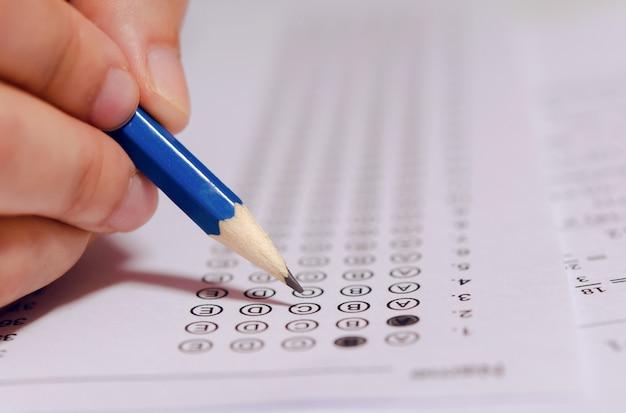 Los estudiantes que sostienen a mano el lápiz escribiendo la opción seleccionada en las hojas de respuestas y las hojas de preguntas de matemáticas. estudiantes que prueban haciendo el examen. examen escolar