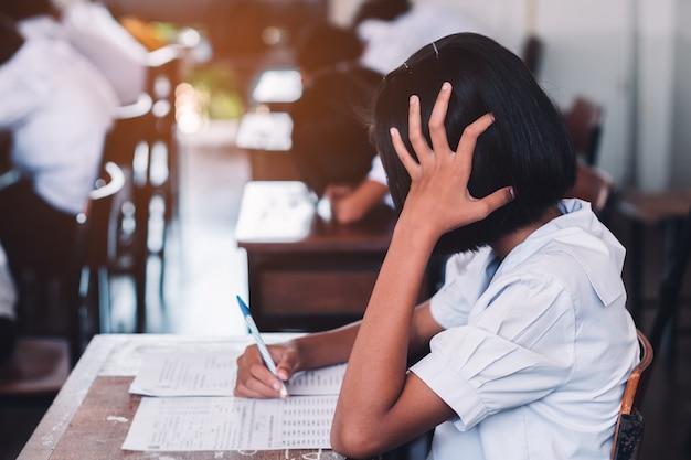 Estudiantes que toman el examen con estrés en el aula de la escuela.