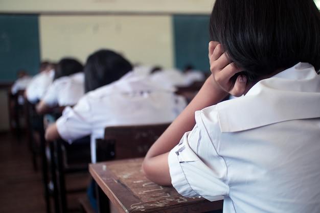 Estudiantes que toman el examen con estrés en el aula de la escuela