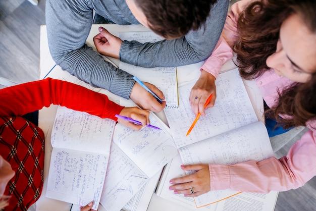 Estudiantes que trabajan en la asignación en la mesa