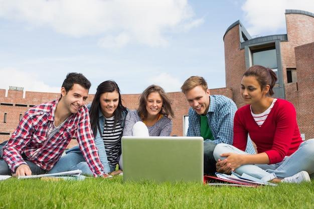 Estudiantes que usan la computadora portátil en césped contra la construcción de la universidad