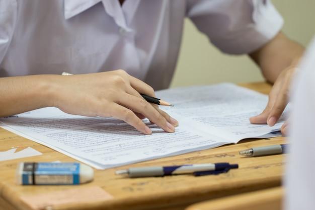 Estudiantes que usan información de lectura con lápiz sobre papel blanco en la escuela secundaria