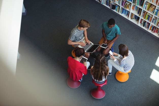 Estudiantes que usan laptop, teléfono móvil, tableta digital en biblioteca