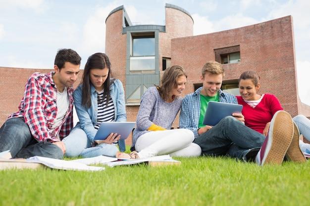Los estudiantes que usan tablet pc en el césped contra la construcción de la universidad