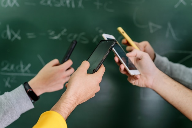 Estudiantes que usan teléfonos móviles en el aula en la pizarra