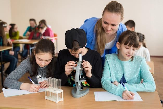 Estudiantes que usan vasos de ciencias y un microscopio en la escuela primaria.