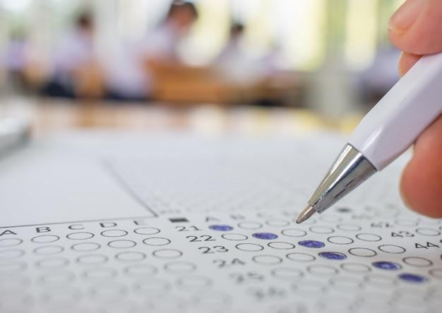 Los estudiantes realizan pruebas de mano haciendo un examen con un bolígrafo