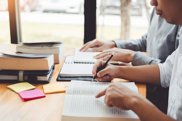 Estudiantes de secundaria o universitarios que estudian y leen juntos en la biblioteca