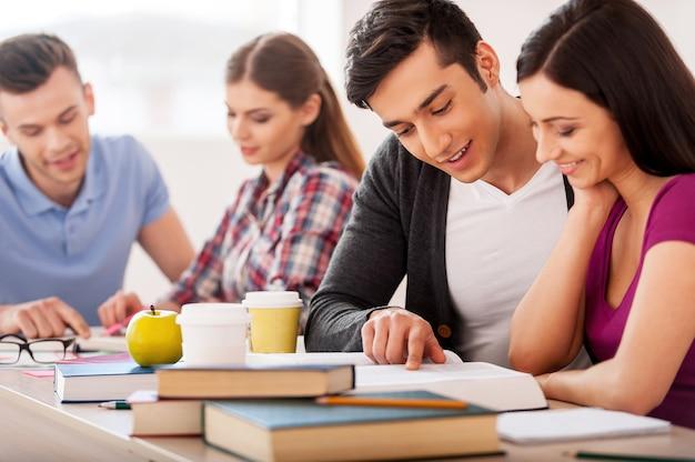Estudiantes seguros. cuatro estudiantes alegres que estudian juntos mientras están sentados en el escritorio