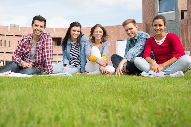 Estudiantes sentados en el césped contra el edificio de la universidad