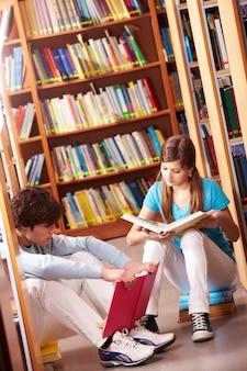 Estudiantes sentados con libros en la biblioteca