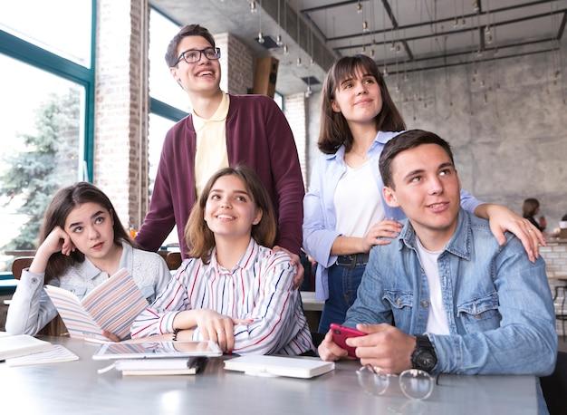 Estudiantes sentados a la mesa con libros y sonriendo.