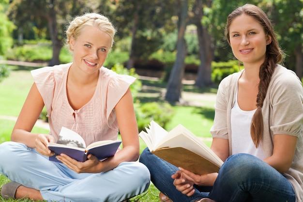 Estudiantes sentados en el parque con sus libros