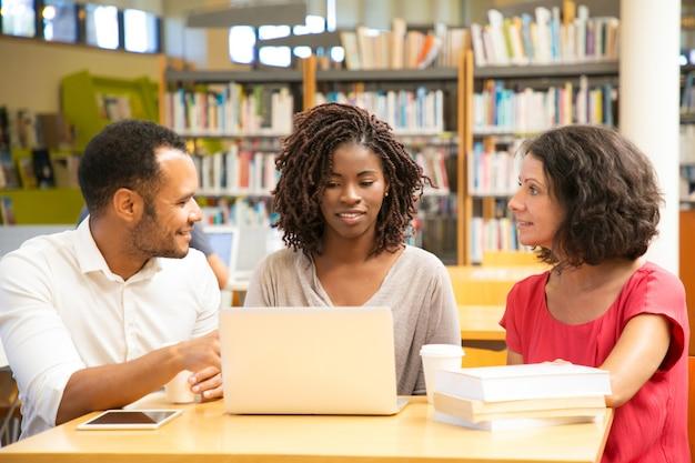 Estudiantes sonrientes discutiendo algo mientras trabajan con la computadora portátil