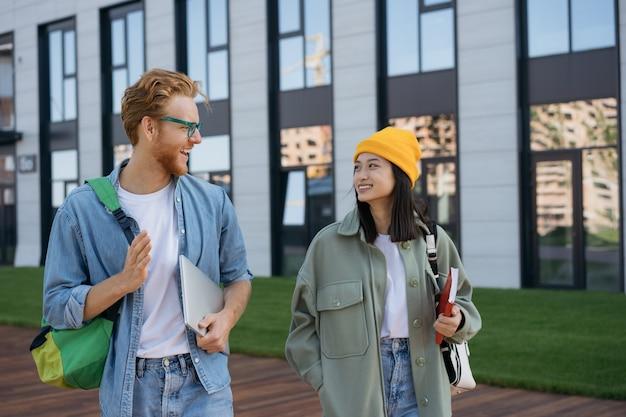 Estudiantes sonrientes con libros y mochilas caminando en el campus universitario