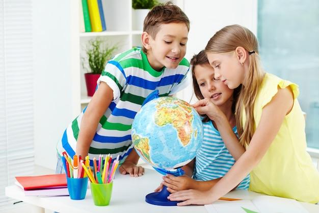 Estudiantes sonrientes mirando el globo terráqueo
