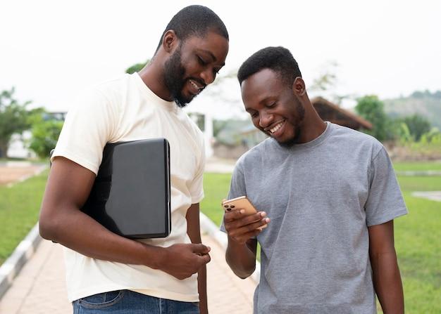 Estudiantes sonrientes de plano medio con dispositivos