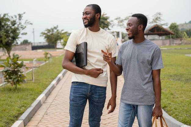 Estudiantes sonrientes de tiro medio en el campus