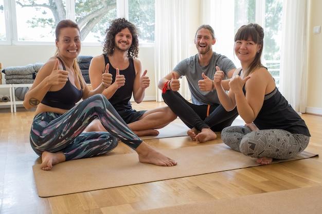 Estudiantes sonrientes de la yoga que muestran los pulgares para arriba