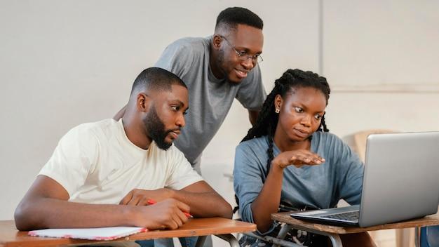 Estudiantes de tiro medio con laptop