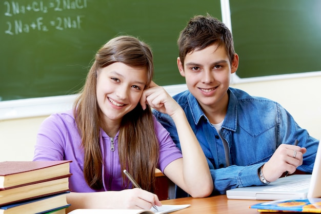 Estudiantes trabajando juntos con la pizarra de fondo