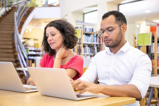 Estudiantes universitarios adultos discutiendo proyecto mientras trabajan