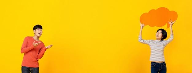 Estudiantes universitarios asiáticos jovenes que juegan en fondo amarillo colorido de la bandera