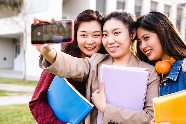Estudiantes universitarios asiáticos tomando un selfie con un teléfono móvil mientras están de pie fuera del campus universitario