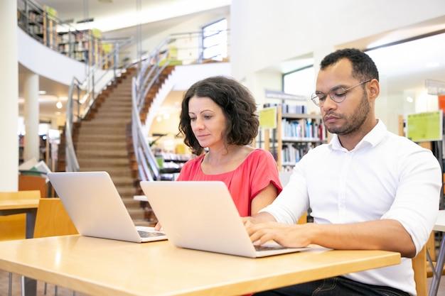 Estudiantes universitarios enfocados que toman el examen en línea