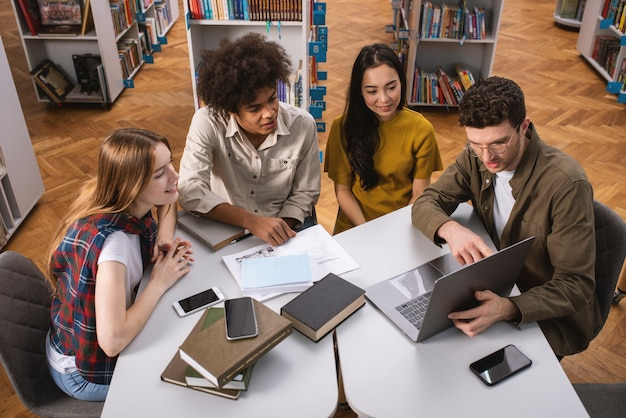 Los estudiantes universitarios están estudiando juntos en una biblioteca.