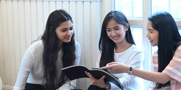Los estudiantes universitarios están hablando y leyendo una revista mientras están sentados juntos en la sala de estar.