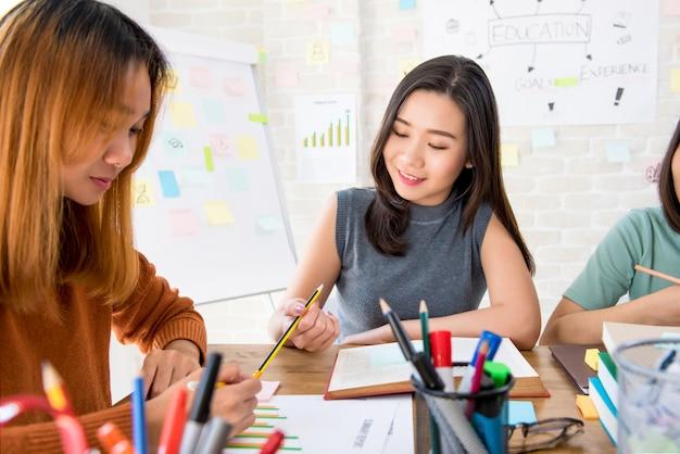 Estudiantes universitarios femeninos de ultramar que hacen la asignación en la sala de clase