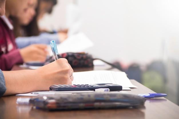 Los estudiantes universitarios hacen cuestionarios, exámenes o estudios del profesor en una gran sala de conferencias. estudiantes en uniforme que asisten al examen en el aula de la escuela educativa.