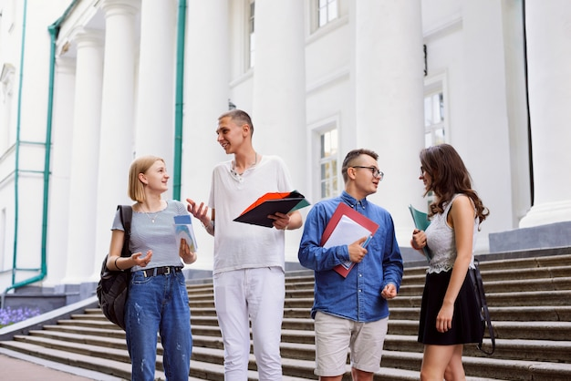 Estudiantes universitarios con libros frente al edificio de la universidad.