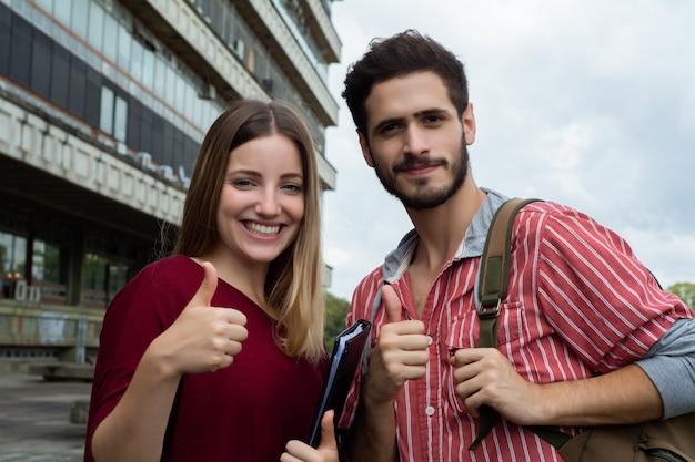 Estudiantes universitarios mostrando los pulgares hacia arriba