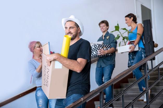 Estudiantes universitarios que se mudan a un nuevo departamento con una caja de cartón y otras cosas. compañeros de cuarto primer día en el campus universitario
